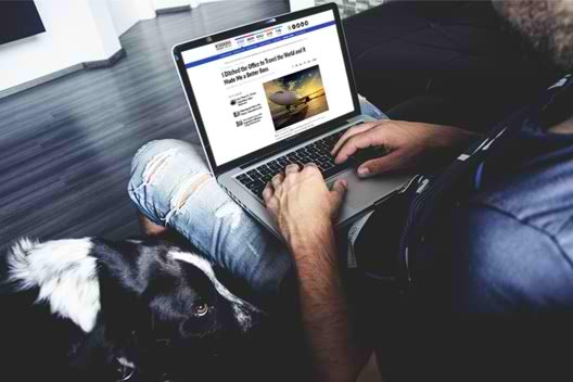 A man reads a TCF byline on Business News Daily as his dog sits close by