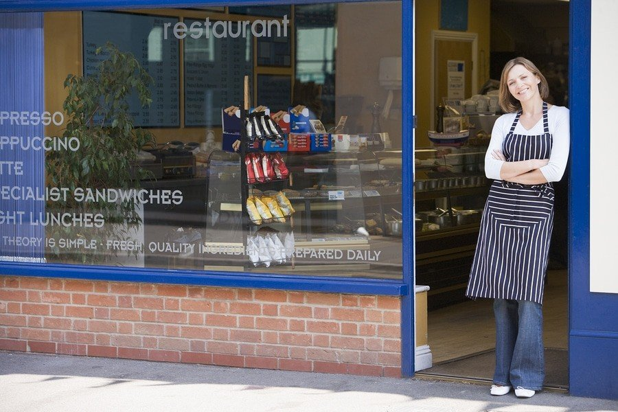 Woman stands in doorway of her own small business.