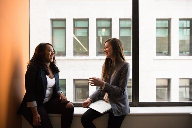 two women sitting on a ledge talking about seo case studies