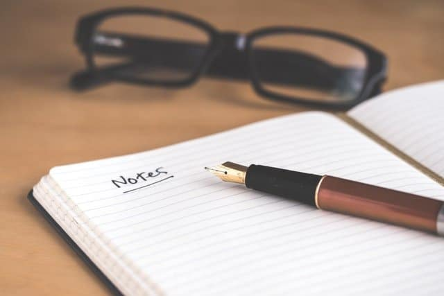 a notepad, glasses, and an ink pen