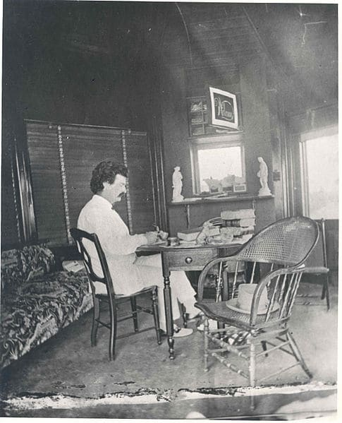 Mark Twain sits at his desk to write in 19th century America.