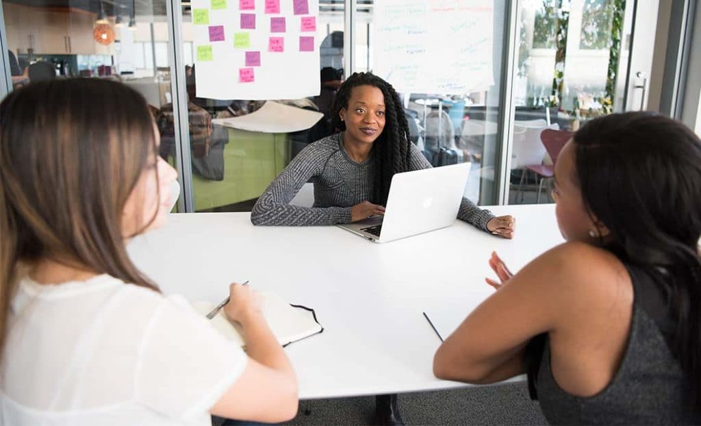 a group of women around a conference table meeting
